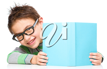Cute little child plays with book and wearing glasses while sitting at table, isolated over white