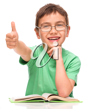 Cute little girl is reading a book and showing thumb up sign, isolated over white