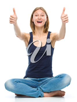 Young happy woman is sitting on the floor and showing thumb up sign using both hands, isolated over white