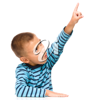 Cute little boy is pointing up using his index finger, isolated over white