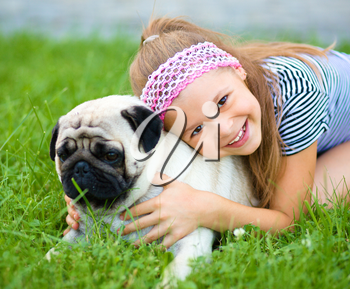 Little girl and her pug dog on green grass, outdoor shoot