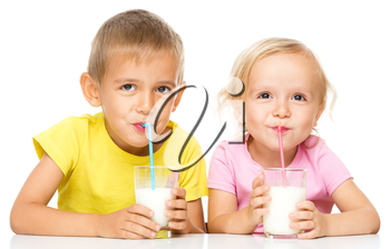 Cute little girl and boy are drinking milk using straw, isolated over white