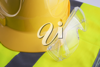Yellow vest and helmet with protection glasses close up