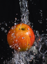 fresh apple in water stream on   black background