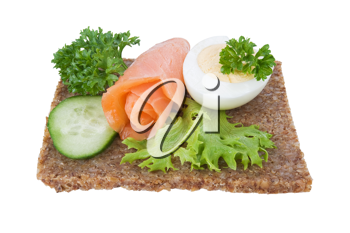 whole grain rye bread sandwich with salmon, egg and vegetables, isolated
