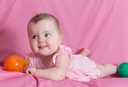 Adorable happy baby girl on pink background