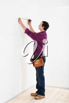 Young worker handyman with measuring tape near the wall in room