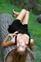 Royalty Free Photo of a Woman Lying on a Tree Trunk