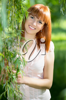 Pretty young red-haired smiling woman posing outdoors