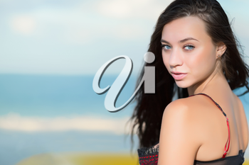 Portrait of beautiful young brunette posing on the beach