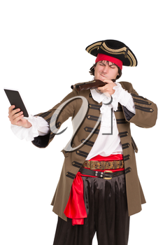Portrait of young man in pirate costume aiming in the tablet. Isolated