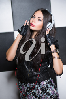 Pretty young brunette posing in the studio with headphones