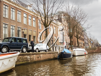 AMSTERDAM,THE NETHERLANDS - FEBRUARY 18, 2012 :   Houses and boats on the canal in Amsterdam . Netherlands