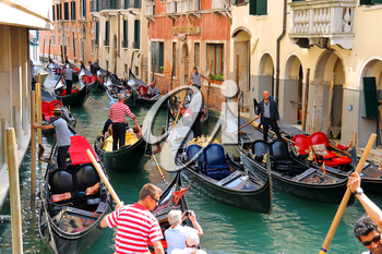 VENICE, ITALY - MAY 06, 2014: Several gondolas with tourists in a narrow channel. Venice, Italy