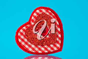 red decorative heart with reflection on blue background