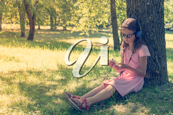 Cute girl listening to music from smartphone