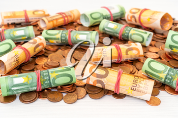 Pile of Euro cents with banknote rolls on top
