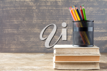 Stack of books with pencil cup on wooden background