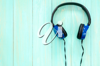 Stereo headphones on blue wooden background with copy-space