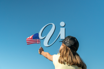 Girl holds an American flag on a sky background