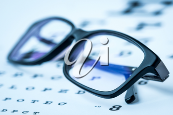 Modern reading glasses on a eye sight test chart. Blue toned image.