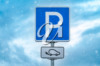 Electric car charging station sign on the snowy sky background