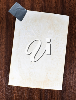 Blank paper sticked on the wooden background