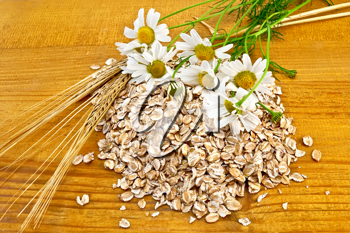 Rye flakes, a bouquet of daisies and stalks of rye on a wooden board