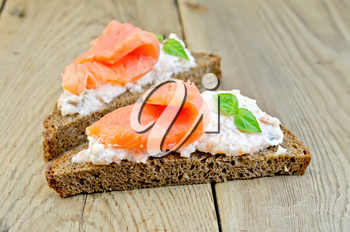 Toast two slices of rye bread with cream, basil and salmon on the background of wooden boards