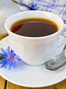 Chicory drink in a white cup with a flower on a saucer and spoon, napkin, milk jug on a wooden boards background