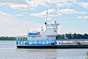 White and blue ferry tug on the background of water, trees, blue sky and white clouds