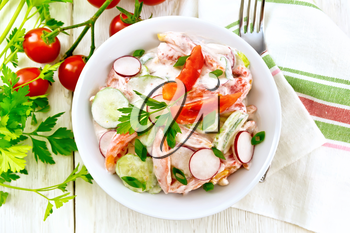 Salad of fresh tomatoes, cucumbers and radish with green onions and parsley,  flavored with mayonnaise and sour cream in a plate, towel and fork on a wooden board background on top