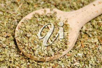 Dried marjoram spice  and wood spoon  as  food background