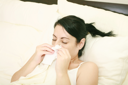 Closeup of gorgeous caucasian woman with cold sneezing into tissue over white background