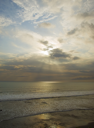 Sun shining though the clouds at sunset at Tanah Lot Temple area, Bali, Indonesia
