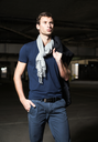 Fashion shot: a handsome young man wearing shirt, scarf and jeans