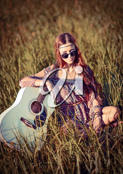Lovely young hippie girl with the guitar sitting on grass
