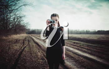 Attractive young girl in black dress taking pictures by the classic film camera. Outdoor portrait in the field
