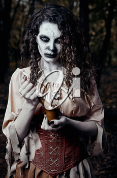 Halloween theme: ugly dread voodoo witch with mortar and pestle. Portrait of the evil hex in dark forest. Zombie woman (undead)