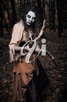 Halloween theme: awful gloomy voodoo witch with staff. Portrait of the evil sorceress in dark grove. Zombie woman (undead)