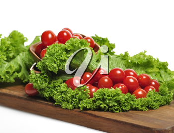 Royalty Free Photo of Tomatoes and Lettuce on a Cutting Board