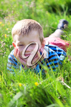 young child laying on the grass