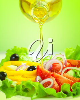 Royalty Free Photo of Oil Being Poured onto a Salad