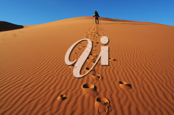 Royalty Free Photo of a Man Walking in the Desert
