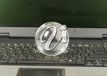 glass globe placed on a laptop