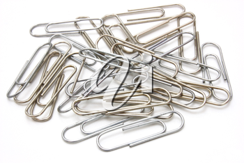 Writing metal paper clips lie in bulk on a white background of a paper