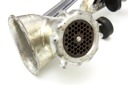 close up of meat grinder on white background