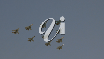 Fighters Su-35 and MiG-29 lined diamond fly with fireworks fly in sky on training parade in honor of Great Patriotic War victory.