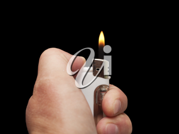 hand with a cigarette lighter on a black background