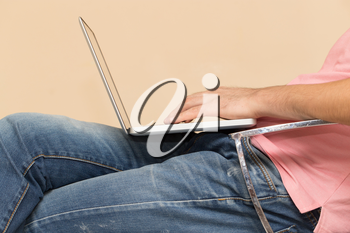 man in jeans with a laptop